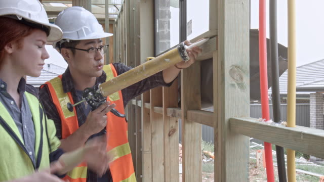 Real time video of asian young man teaching woman how to seal with silicon at construction site