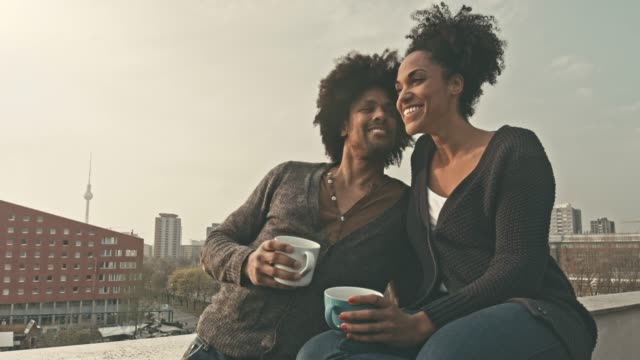 real time video of black couple enjoying sunset in the terrace with coffee - patio stock videos & royalty-free footage