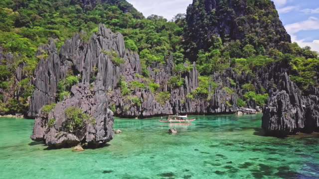 real time video of boat arriving at the transparent waters of ubugon island, palawan, philippines - filippine video stock e b–roll