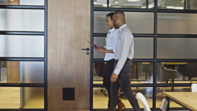 vídeos de stock e filmes b-roll de real time video of business people discussing over digital tablet whole walking in the office - africa