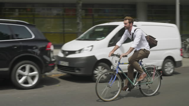 vídeos de stock e filmes b-roll de real time video of businessman commuting by bicycle in the streets of berlin - homens de idade mediana