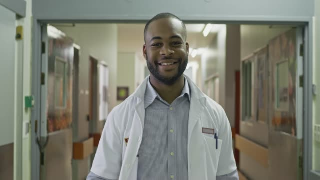 real time video of cheerful young male doctor walking in the hospital corridor - nurse stock videos & royalty-free footage