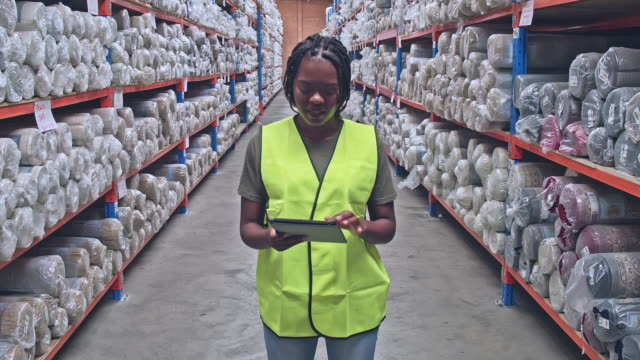 real time video of female worker holding digital tablet in rug warehouse - occupational safety and health stock videos and b-roll footage
