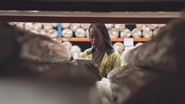 Real time video of female worker with digital tablet at warehouse