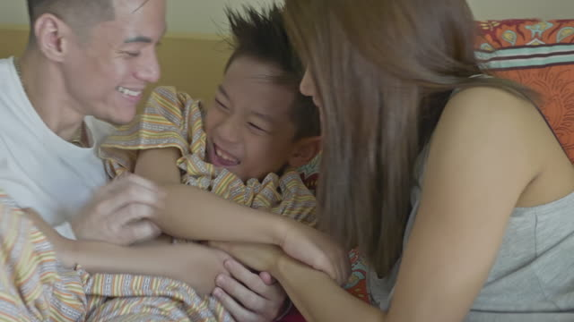 vidéos et rushes de vidéo en temps réel de la famille philippine bénéficiant d'être ensemble - chatouiller