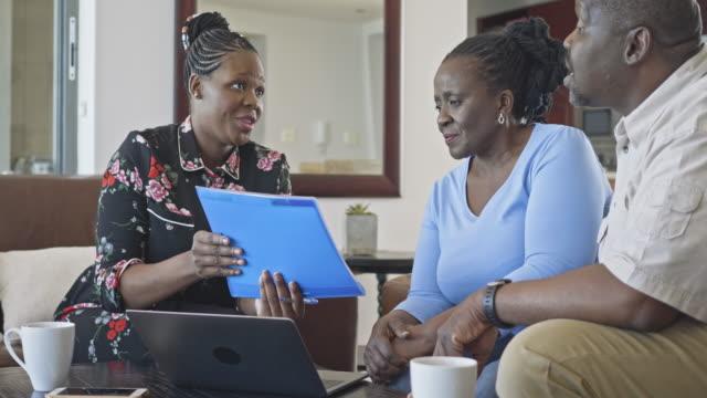 vídeos de stock e filmes b-roll de real time video of financial advisor showing document to senior couple at home - 55 59 anos