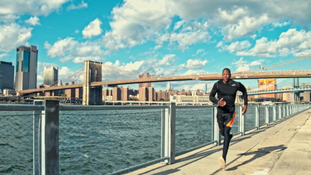 real time video of fit man jogging in new york, usa - brooklyn bridge stock videos and b-roll footage
