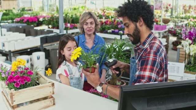 real time video of gardener using barcode scanner by family at shop - garden center stock videos and b-roll footage