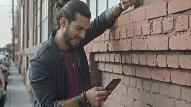 Real time video of handsome man leaning on brick wall reading a message on the mobile phone