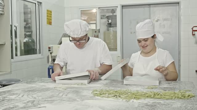 vidéos et rushes de vidéo en temps réel des travailleurs hispaniques de pâtes mettant fettuccine fariné dans des boîtes - s'impliquer à fond