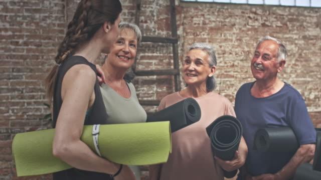 echtzeit-video der kursleiter, die ankunft in der yoga-kurs - trainer stock-videos und b-roll-filmmaterial