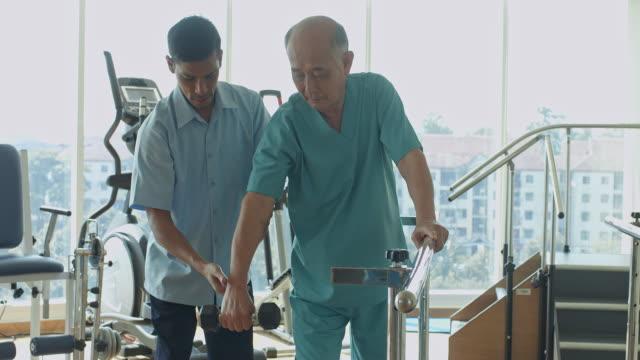 vídeos de stock, filmes e b-roll de vídeo em tempo real de enfermeiro, ajudando o homem sênior na sessão de fisioterapia, utilizando o peso da mão - fisioterapeuta