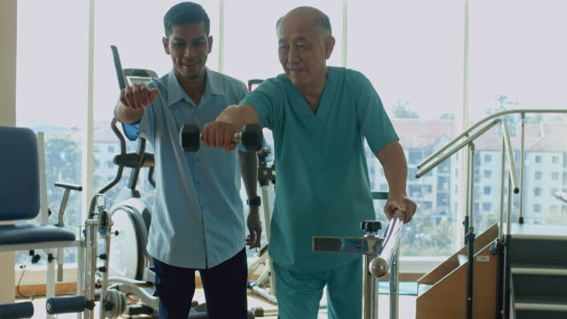 real time video of male nurse showing senior man in physiotherapy session using hand weight - care stock videos & royalty-free footage