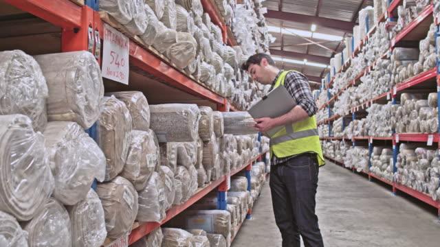 Realtidsvideo av manliga arbetare med checklista att undersöka mattor
