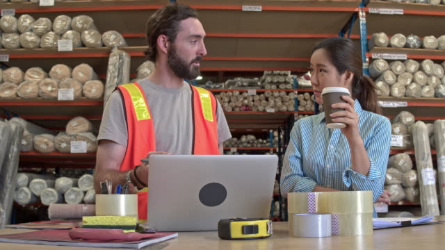 Real time video of manager talking to worker with laptop at warehouse