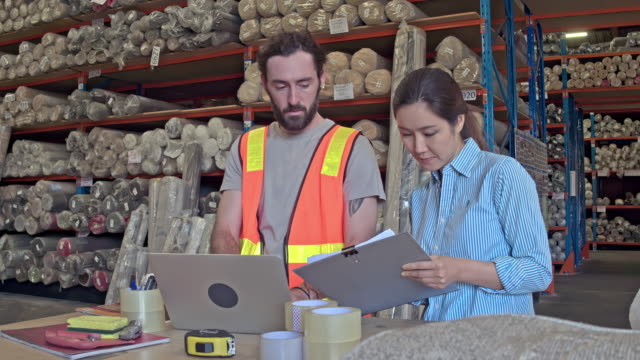 real time video of manager talking to worker with laptop at warehouse - warehouse stock videos and b-roll footage