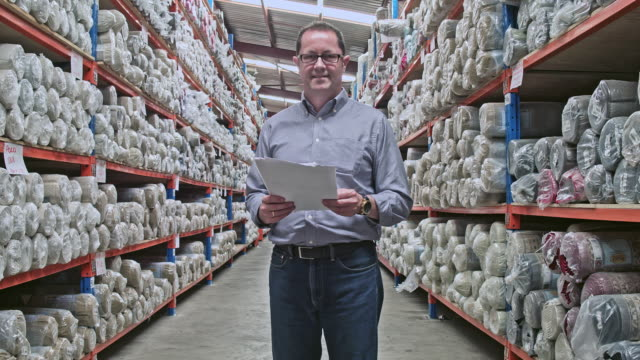 Real time video of manager with digital tablet at warehouse