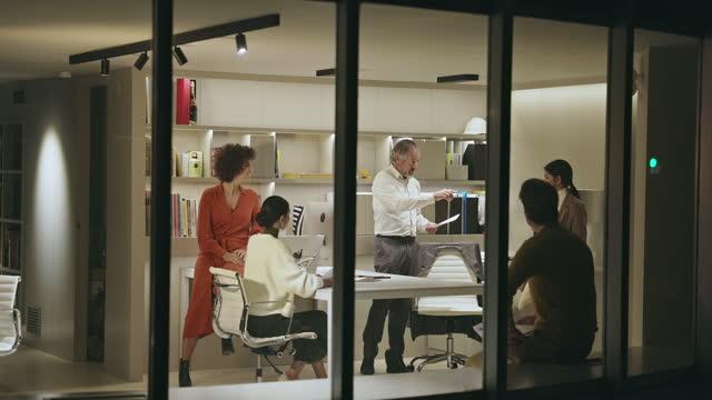Vídeo em tempo real de empresário maduro conversando com colegas no escritório tarde da noite