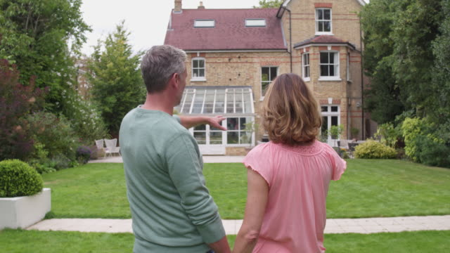 Real time video of mature couple standing in front of house talking about buying it