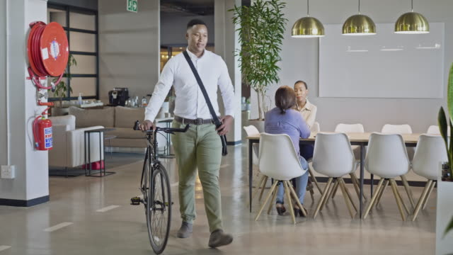 real time video of millennial businessman arriving to the office with his bicycle - commuter stock videos & royalty-free footage