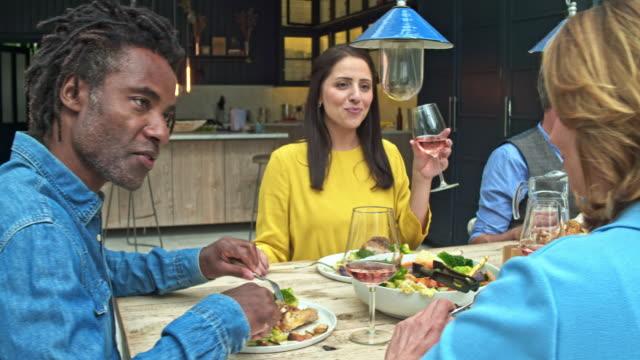 Realtidsvideo av multietnisk grupp av vänner som äter lunch hemma