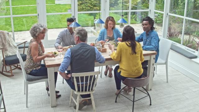 Vidéo en temps réel du groupe multiethnique des amis en train de déjeuner à la maison