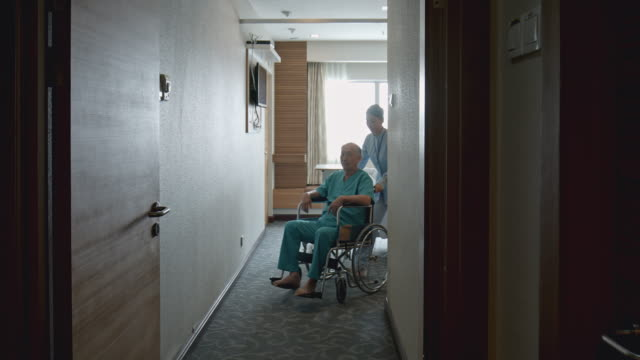 Real time video of nurse taking patient into a health test from hospital room with wheelchair