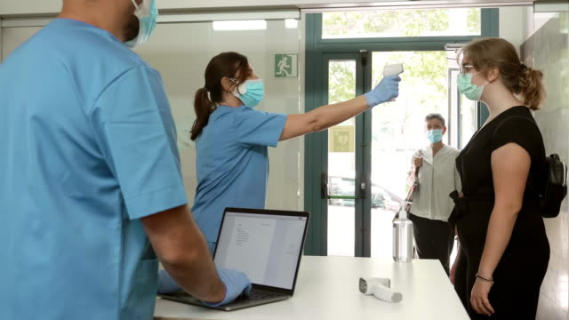real time video of pandemic control measures in hospital entrance - fare la fila video stock e b–roll