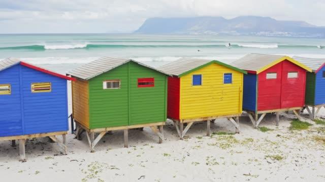 vídeos de stock e filmes b-roll de real time video of people surfing at muizenberg beach with colourful beach huts , cape town, south africa - cabana estrutura construída