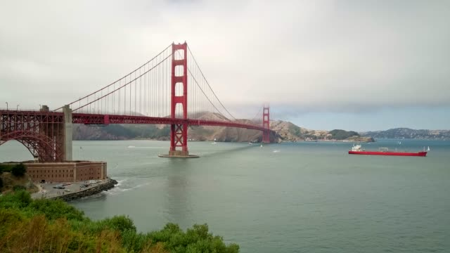 real time video of ship crossing golden gate bridge on a cloudy day - golden gate bridge stock videos & royalty-free footage