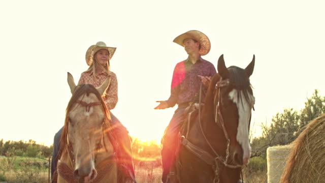 Real time video of siblings riding horses at sunset in Utah, USA