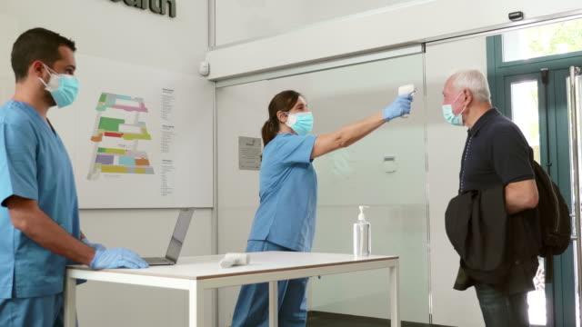 vidéos et rushes de vidéo en temps réel des mesures de contrôle de la température à l'entrée de l'hôpital pour la pandémie - cold temperature