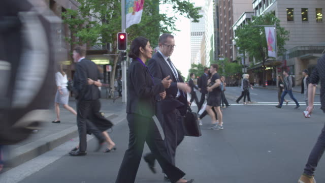 real time video of two business people crossing the street commuting to work - sydney australia stock videos and b-roll footage