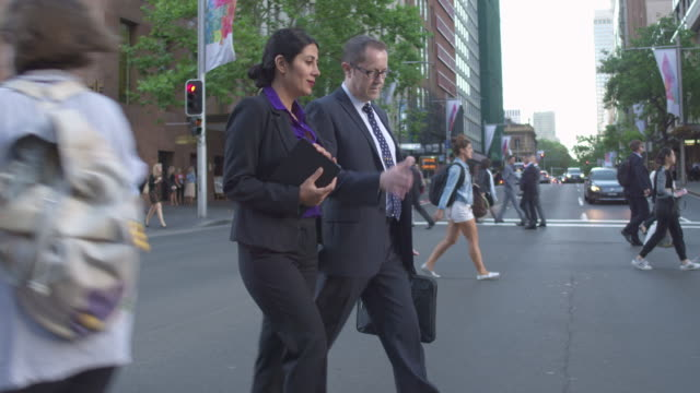 vídeos de stock e filmes b-roll de real time video of two business people crossing the street commuting to work - fato