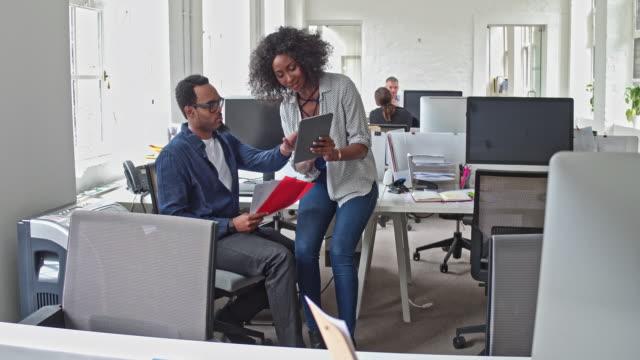 vídeos de stock, filmes e b-roll de vídeo em tempo real de duas pessoas de negócios, discutindo com tablet digital no escritório - dispositivo de informação portátil