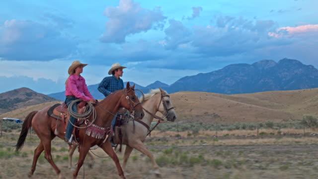 echtzeit-video von zwei freunden reiten in der abenddämmerung in utah. - ranch stock-videos und b-roll-filmmaterial