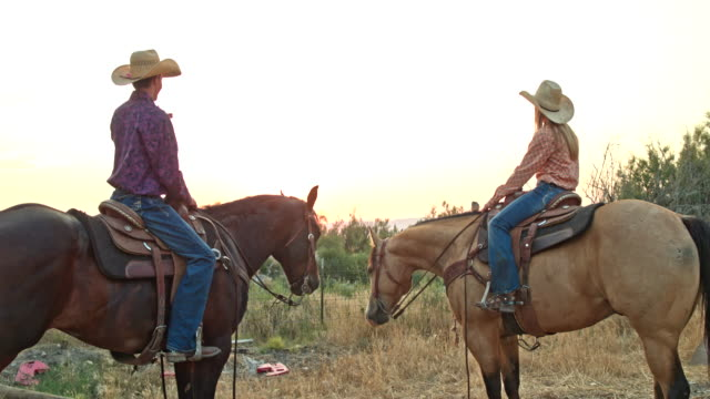real time video of two teenagers riding horses at sunset - cowgirl stock videos & royalty-free footage