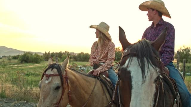 stockvideo's en b-roll-footage met real-time video van twee tieners paardrijden paarden bij zonsondergang - hoofddeksel