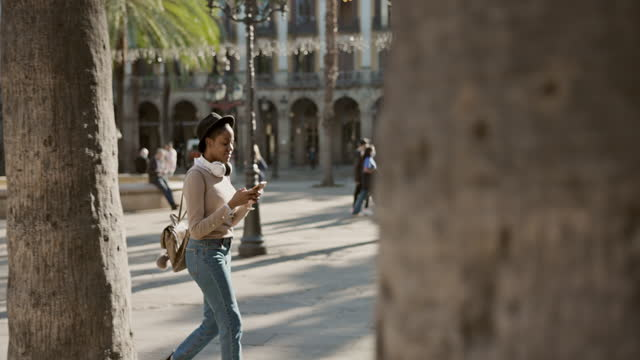 real time video of woman exploring the city checking mobile phone for guidance - side view stock videos & royalty-free footage