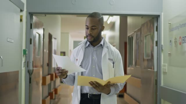 real time video of young male doctor walking in the hospital corridor checking some documents - medical student stock videos and b-roll footage
