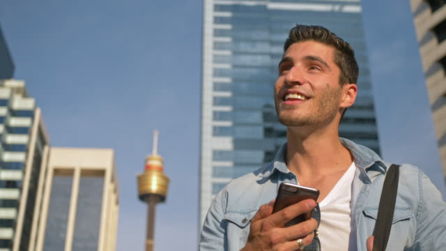 Real time video of young man holding mobile phone while walking in city