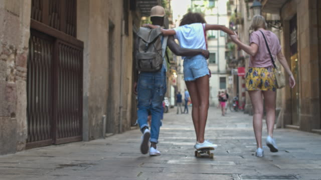 vídeos de stock e filmes b-roll de real time video of youngsters with skateboards walking on urban street - espanha