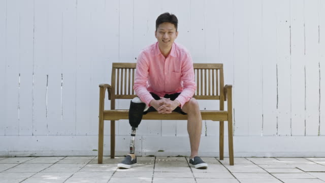 vídeos de stock e filmes b-roll de real time video portrait of smiling japanese disable man sitting on bench - full length