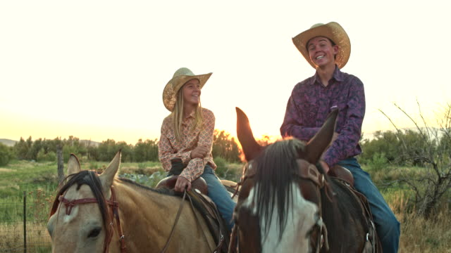 Real time video portrait of two teenagers riding horses at sunset