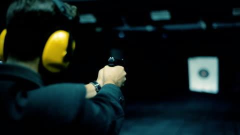vidéos et rushes de vidéo en temps réel tourné d'un jeune homme méconnaissable tirant au champ de tir - cool