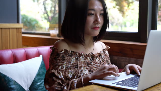 real time young smiling asian girl is playing laptop and enjoying coffee in cafe - coffee drink stock videos & royalty-free footage