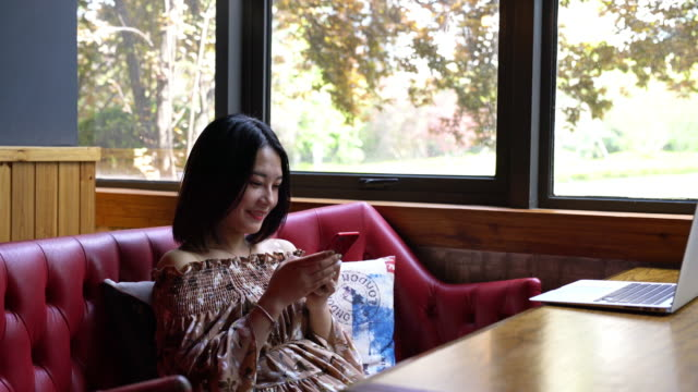 real time young smiling asian girl is playing mobile phone and enjoying coffee in cafe - coffee drink stock videos & royalty-free footage
