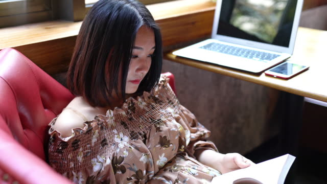 real time young smiling asian girl reading and enjoying coffee in cafe - coffee drink stock videos & royalty-free footage