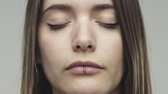 灰色の背景に目を閉じて本物の女性