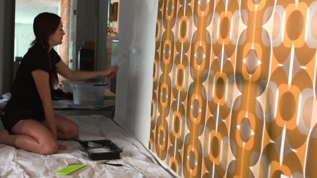 vídeos y material grabado en eventos de stock de real woman improving, renovating and decorating her home by hanging 1970's retro wallpaper - reforma